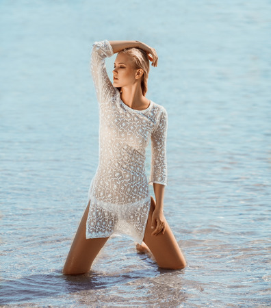 Girl in white transparent dress and bikini on sea background. She stands with flowing hair and looks away.