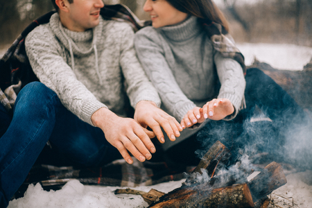 warms: Young woman and man warms their hands over bonfire during winter picnic. Close-up. Stock Photo