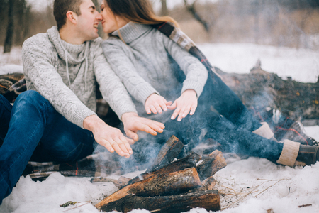 warms: Young woman and man warms their hands over bonfire during winter picnic. They are kissing.