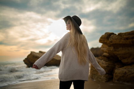 Woman in hat and sweater on winter beach at sunset. She looks pensively at sea. Clouds at sunset sky background and rocks are visible from behind. Stock Photo