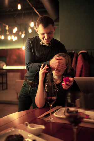 the case before: Young man makes woman marriage proposal, he closed her eyes with his hand and holds in front of her jewelry case with engagement ring. Before them is table with food and glasses of wine.