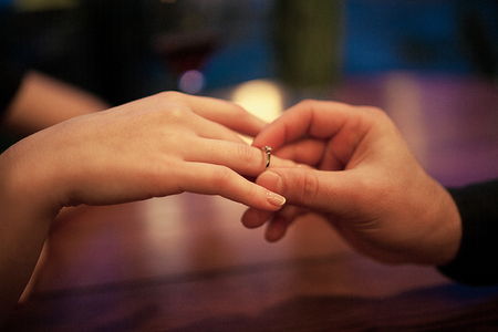 fingers put together: Young man makes woman marriage proposal and puts an engagement ring on her finger. Close up. They are sitting at table. Stock Photo