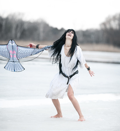 Crazy young woman standing on ice lake with kite in her hand. She is madly laughing.