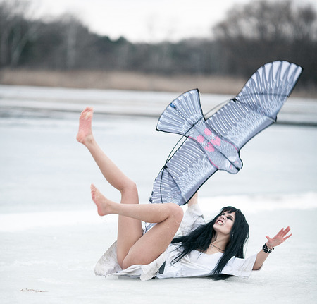 Crazy young woman lies on ice lake and pulls her feet with a kite in her hand. Her face is seen anger and aggression.