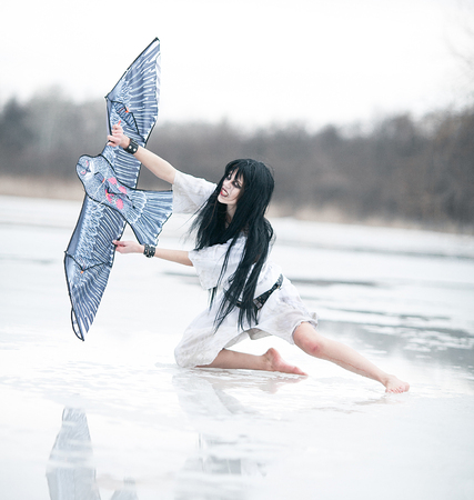 daft: Crazy young woman sitting on ice lake with kite in her hand. Her face is seen anger and aggression. Stock Photo