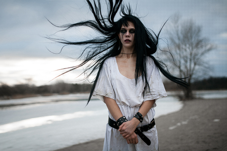 Portrait of crazy young woman with hair blown up by wind near lake. Hair flies in all directions.
