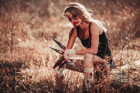 photomanipulation: Mutant girl in wounds and ulcers with claws instead of fingers. She is sitting. Stock Photo