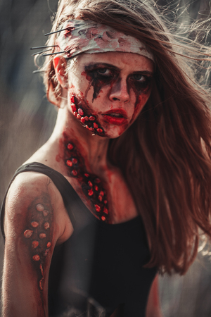 photomanipulation: Mutant girl portrait in wounds and ulcers with nails in her head. On her head is bandage.