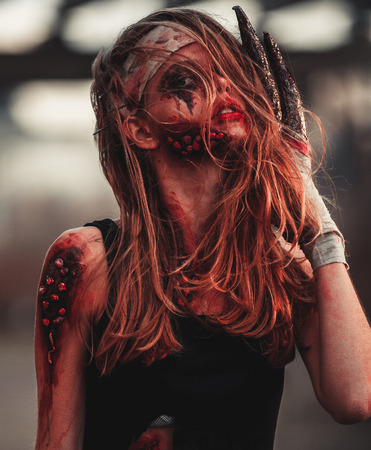 photomanipulation: Mutant girl portrait in wounds and ulcers with nails in her head and claws instead of fingers. On her head and hands is bandage.
