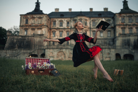 Woman sorceress flies in air and reads book against backdrop of ancient castle. Levitation. On grass there is suitcase with flowers.