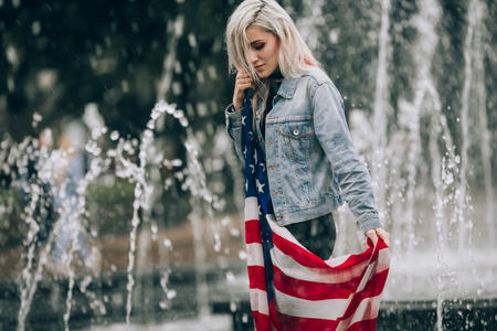Young woman holds an American flag against fountain background.