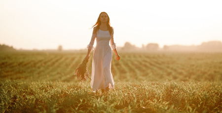 Young woman in long white lace dress on cornfield. She goes with bouquet of wild flowers in her hands.