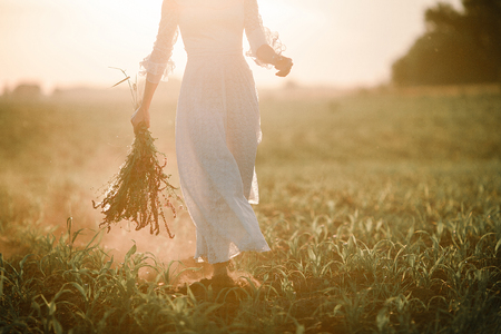 Young woman in long white lace dress on cornfield at sunset. She goes barefoot with bouquet of wild flowers in her hands.  Stock Photo