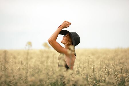sunburnt: Young woman in black dress and hat among flowering meadow. She smiles. Stock Photo