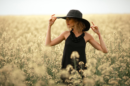 Young woman in black dress and hat among flowering meadow. She looks away thoughtfully. Stock Photo