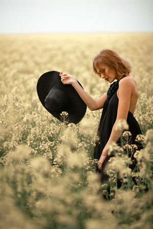 Young woman in black dress and hat in her hand among flowering meadow. She looks thoughtfully.