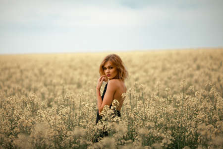 looked: Young woman in black dress among flowering meadow. She turned around and looked at camera.