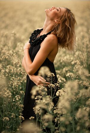 Happy young woman in black dress among flowering meadow. She is very joyful, cheerful and laughs.
