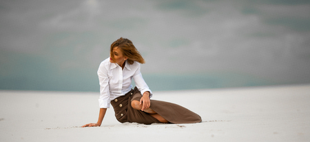Young woman sits on sand in desert and pensively looks aside. She is dressed in long skirt and blouse.