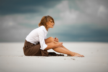Young sad and pensive woman sits on sand in desert. She is dressed in long skirt and blouse.