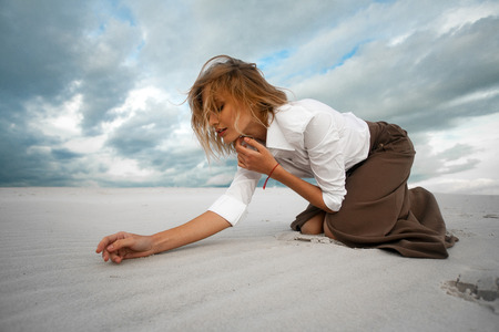 Young sad woman kneeling in the desert on sky background. She is dressed in long skirt and blouse.