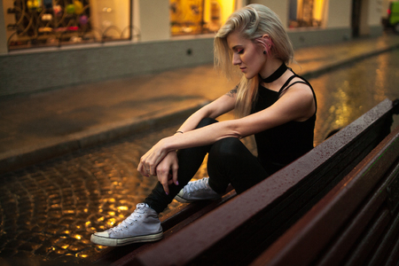 Young woman sits on wet bench on city street in evening in rain. In background there are lights of night city and reflections on wet pavement. Stock Photo