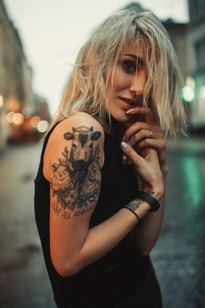 Young woman portrait with tattoo on shoulder standing on city street in evening. In background there are city lights.
