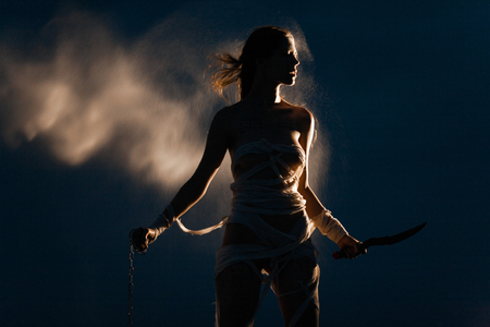 Girl in image of Egyptian mummy stands with metal chain and knife in her hands. She is wrapped in bandages. Around her flies glowing sand in air. Her silhouette illuminated