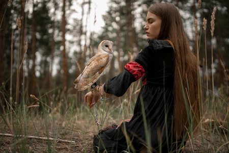 Girl with long hair in red and black dress sits on grass with owl on her hand in forest. Owl is tied to her arm by chain.