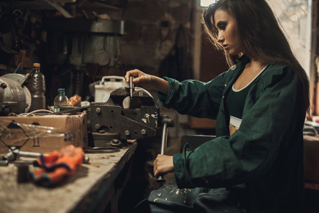 Girl worker in green overalls sits in workshop near vice. In vice she clamps detail. Banco de Imagens