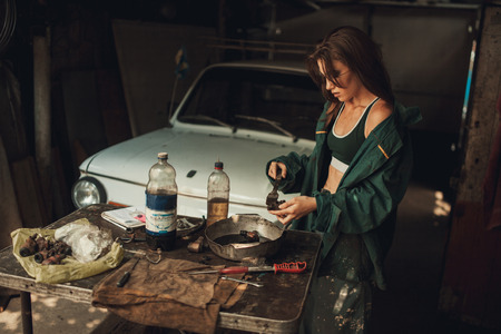 lubricate: Girl worker in green overalls and t-shirt stands in workshop among tools and lubricates  spare parts from car. In her hands she holds brush, next to her there is bottle of grease. Stock Photo