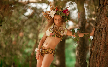 Beautiful little girl in image of nymph dryad with floral head wreath stands near tree in magical fairytale forest . Stock Photo
