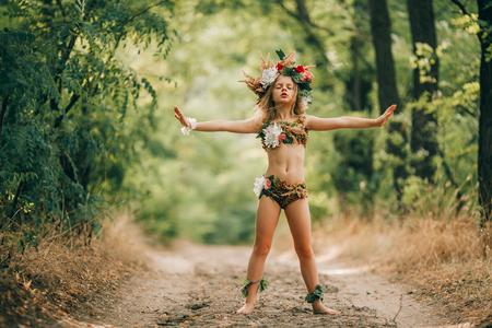 Het mooie meisje in beeld van nimf dryade met bloemen hoofdkroon bevindt zich in bosweg en werkt. Stockfoto
