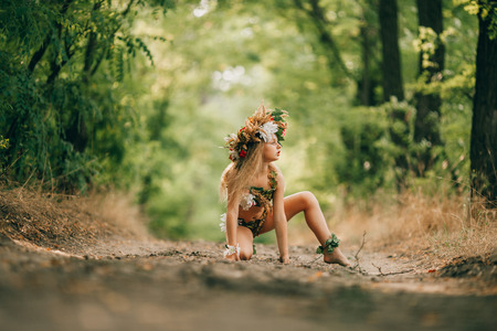 Beautiful little girl in image of nymph dryad with floral head wreath sits in forest road. Stock Photo - 84048922
