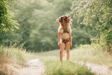 spica: Beautiful little girl in image of nymph dryad with floral head wreath stands in forest road. Close up.