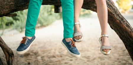少女と少年は木の枝に並んで座る。最初が大好きです。自分の足だけが表示されます。