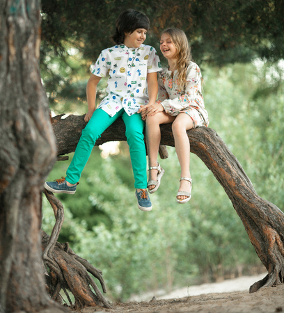 Little girl and boy sit side by side on tree branch and laughing cheerfully. First love.