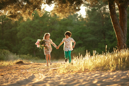 Little girl with bouquet and boy are running in sunny forest road and holding hands. First love.