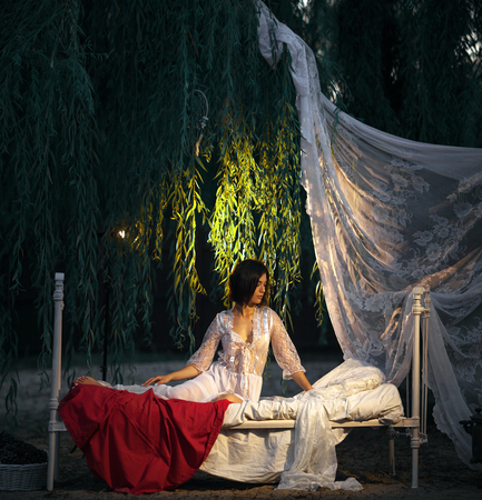 Young sexy woman in lacy peignoir sits on bed with bedding and baldachin near tree at evening. She is lit by lamp. Concept of rest, relaxation and serenity.