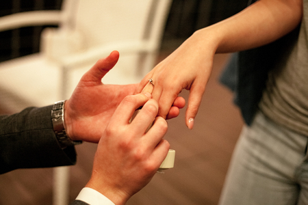 fingers put together: Man makes woman marriage proposal and puts on engagement ring with diamond on her finger. Close up.