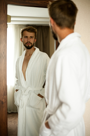 mirror image: Young man in white bathrobe stands in front of mirror and looks at his reflection.. Stock Photo
