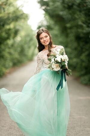 Bride in beautiful wedding dress smiles and goes on forest road with bouquet in hands.
