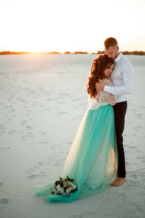Bride and groom stand in desert, smile and embrace. They standing on background of white sand and sunset. Bouquet lies on hem of wedding dress.
