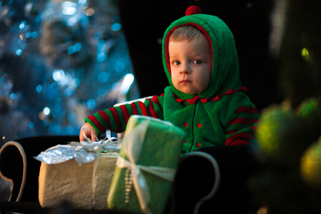 Little boy in green hood sits in black armchair with Christmas gift boxes on background of celebration lights.