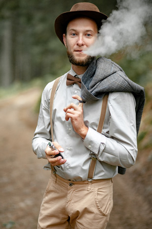 Young man in stylish clothes and hat stands on background of forest and smokes electronic cigarette with smoke.