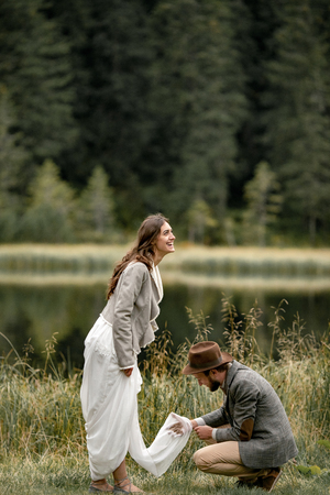Groom cleans dirty hem of brides dress and they laugh happily near forest lake in Carpathian mountains. Stock Photo