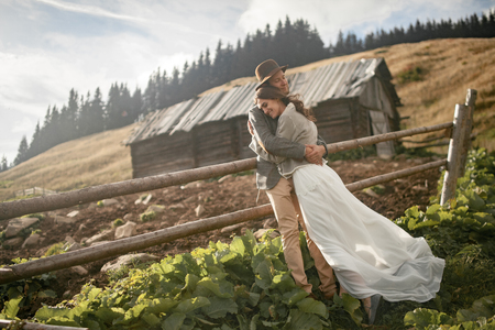 Newlyweds stand, smile and hug during honeymoon trip on background of old wooden hut and fence in Carpathian mountains.  Stock Photo