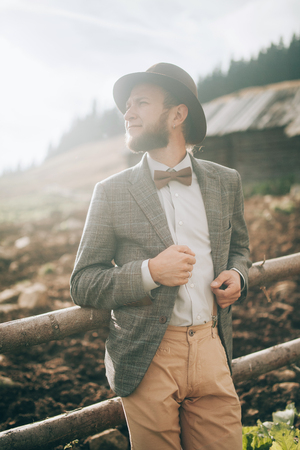 Young man in stylish clothes and hat stands on background of old wooden hut and fence in Carpathian mountains. Closeup.