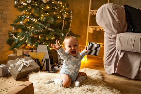 Little baby boy is happy with Christmas gift. He sits, laughs cheerfully and holds Christmas gift in his hand.