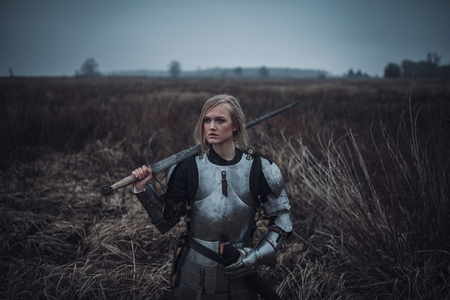 Girl in   armor and with sword in her hands stands on meadow in middle of dry grass. Closeup.